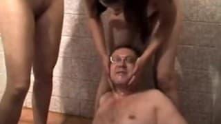 Zwei junge Frauen pissen auf einen reifen Mann