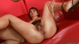 Reife Brünette squirtet auf dem roten Sofa