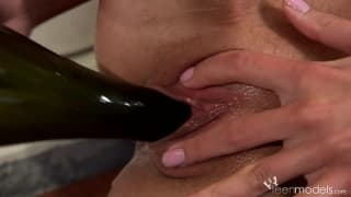 Die blonde Kate A masturbiert mit Weinflasche