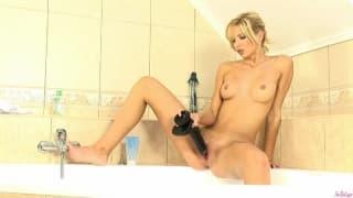 Eine hübsche Blondine masturbiert im Bad