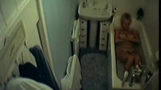 Diese Frau zeiht sich in der Badewanne aus.