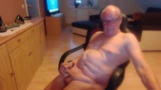 Alter Mann, der auf einem Stuhl wichst