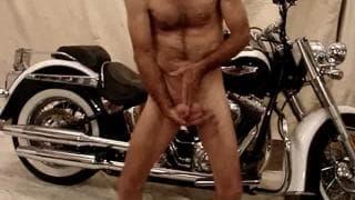 Er strippt sich vor dem Motorrad nackt