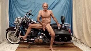 Alter Mann zeigt langen Schwanz auf Motorrad